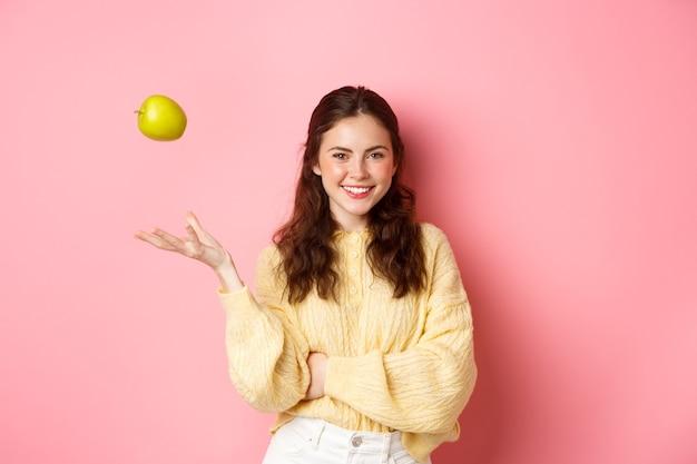 Молодая улыбающаяся женщина смотрит с уверенностью, подбрасывает яблоко в воздух, ест здоровые фрукты, чтобы сохранить идеальную улыбку, стоя у розовой стены