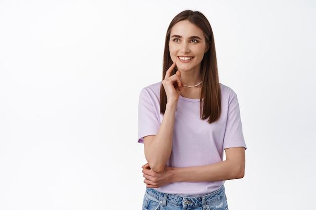 若い笑顔の女性は、興味を持って見て、決心し、彼女の決定を下し、満足し、満足している表情で左を見つめ、白の上に立っています