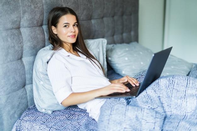 彼女のラップトップの前でベッドに横たわって若い笑顔の女性
