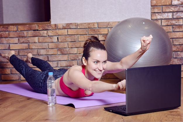 Young smiling woman lying on fitness mat depicts the flight of a superhero during the warm-up before training online with videos on the laptop. funny home fitness