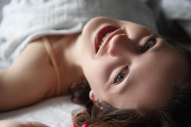Молодая женщина улыбается, лежа в постели и глядя вверх
