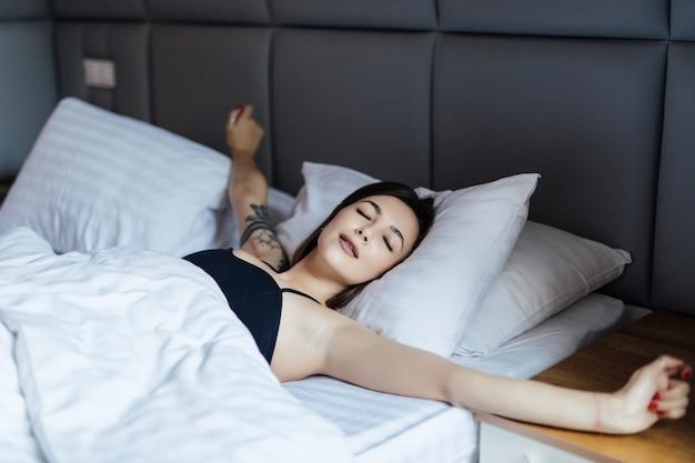 침대에 누워 그녀의 팔을 스트레칭 젊은 웃는 여자