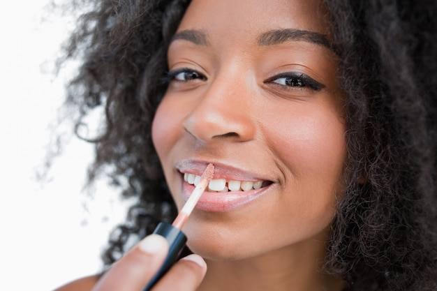 Young smiling woman making-up while using a lip gloss applicator
