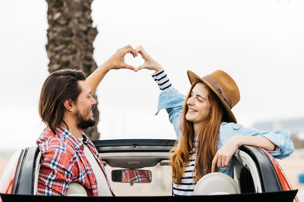 Young smiling woman and man showing symbol of heart and leaning out from automobile