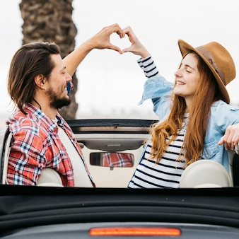 Young smiling woman and man showing symbol of heart and leaning out from car