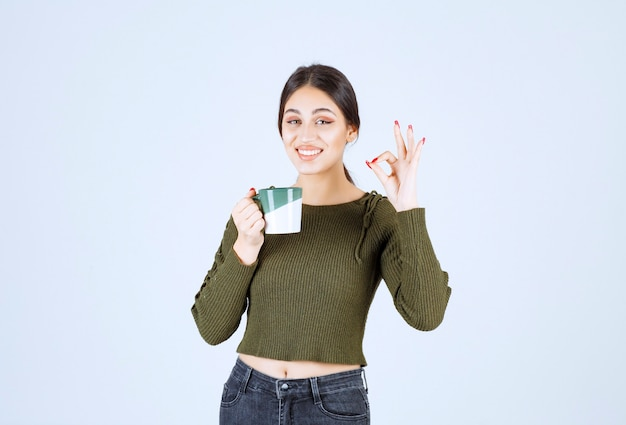 A young smiling woman model holding a cup and showing ok gesture .