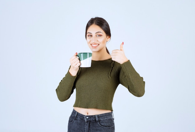 A young smiling woman model holding a cup and showing a thumb up .