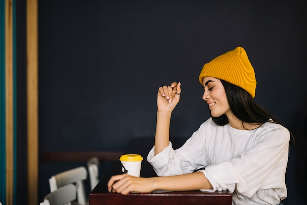 Young smiling woman near cup of drink at table