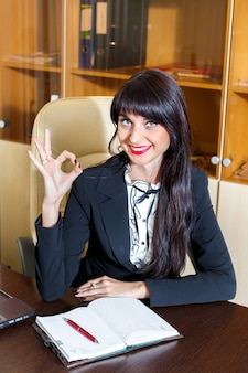 Young smiling woman in office showing okay symbol