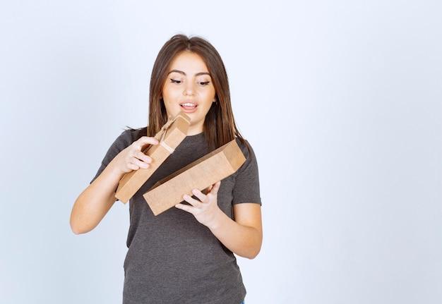 선물 상자를 여는 젊은 웃는 여자.