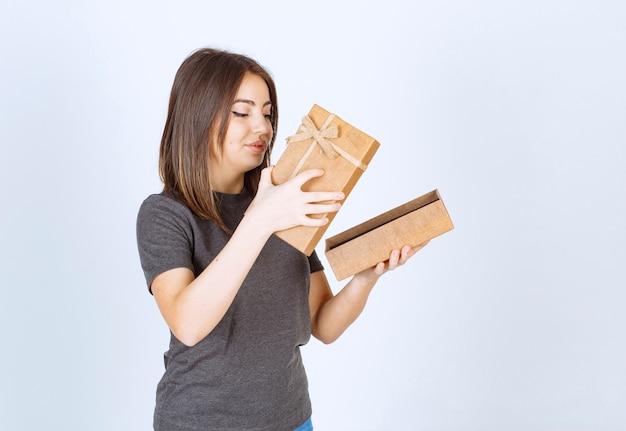 Giovane donna sorridente che apre una confezione regalo.