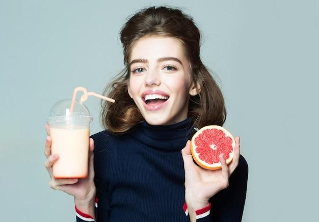 젊은 웃는 여자 또는 귀여운 섹시한 여자 회색 복사 공간에 짚 포즈와 병 또는 유리에서 신선한 주스를 마시는 자몽 과일을 보유