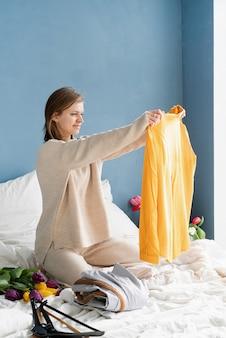 Молодая улыбающаяся женщина организует одежду, сидя на кровати у себя дома