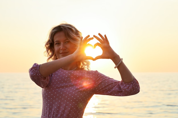 Young smiling woman in pink dress with heart-shaped fingers stands at sunset