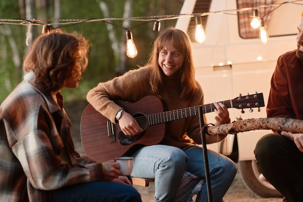 Young smiling woman playing guitar and singing songs together with her friends on a picnic