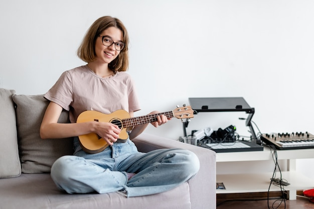Young smiling woman playing ukulele at home