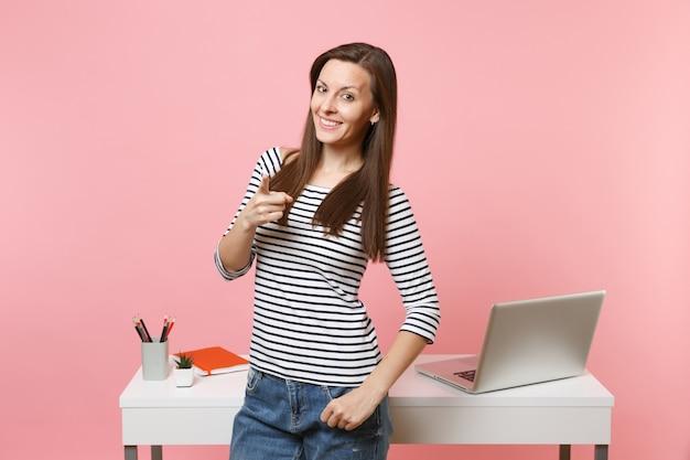 人差し指を前に向ける若い笑顔の女性。仕事とラップトップで白い机の近くに立って