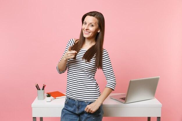 カメラワークに人差し指を指して、パステルピンクの背景で隔離のラップトップと白い机の近くに立っている若い笑顔の女性。業績ビジネスキャリアコンセプト。広告用のスペースをコピーします。
