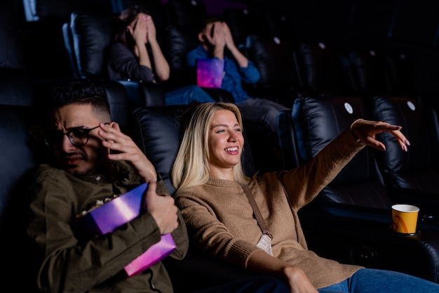 Young smiling woman pointing at large screen while watching action movie with her boyfriend holding box of popcorn