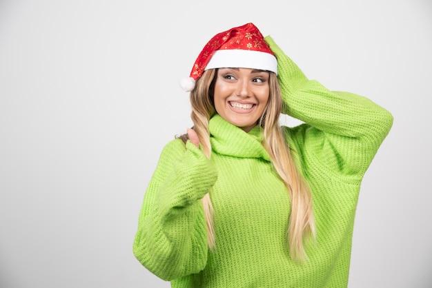 산타 클로스 빨간 모자에 포즈 젊은 웃는 여자.