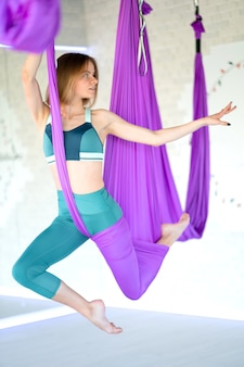 Young smiling woman practice in aero stretching swing. aerial flying yoga exercises practice in purple hammock in fitness club.