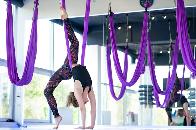 若い笑顔の女性は、エアロストレッチスイングで練習します。空中飛行ヨガの練習は、フィットネスクラブの紫色のハンモックで練習します。