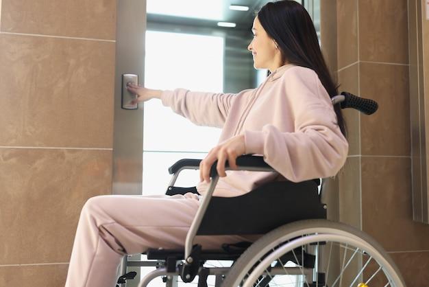 젊은 웃는 여자 프레스 엘리베이터 버튼 근접 촬영