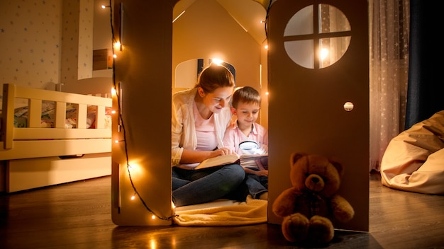 Young smiling woman reading story to her little son at night