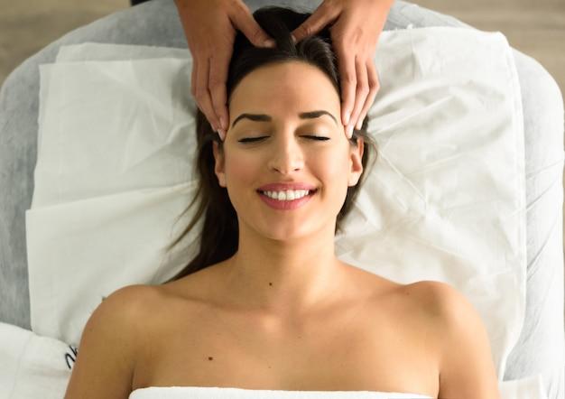 Молодая женщина улыбается получать массаж головы в спа-центре.