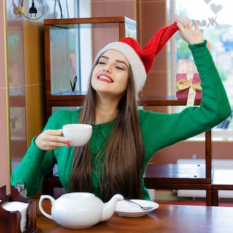 Young smiling woman in red santas hat drinking tea in cafe