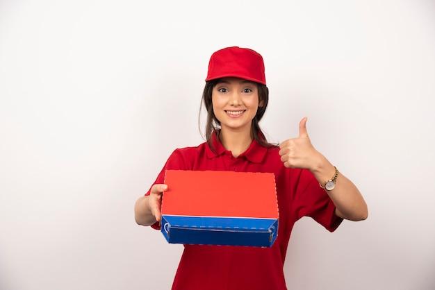 Giovane donna sorridente in uniforme rossa che consegna pizza in scatola.