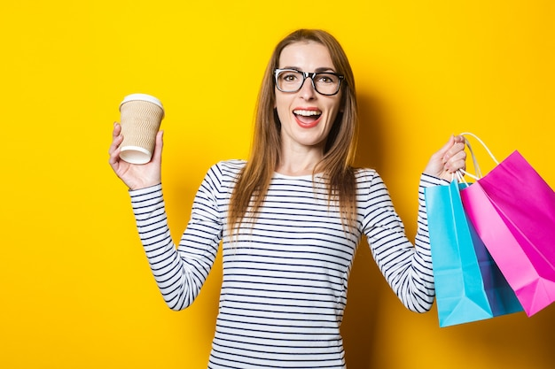 若い笑顔の女性は黄色の背景にコーヒーとバッグと紙コップを持って喜ぶ