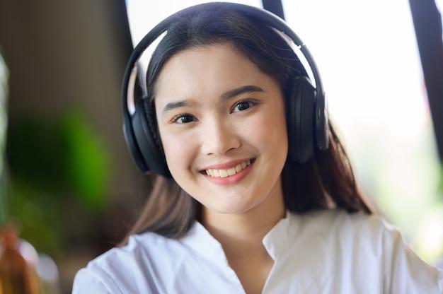 Молодая улыбающаяся женщина расслабляется и слушает музыку в наушниках