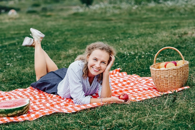 Молодая улыбающаяся женщина отдыхает на открытом воздухе и устраивает пикник, она лежит на одеяле из красных клеток на траве на лугу.