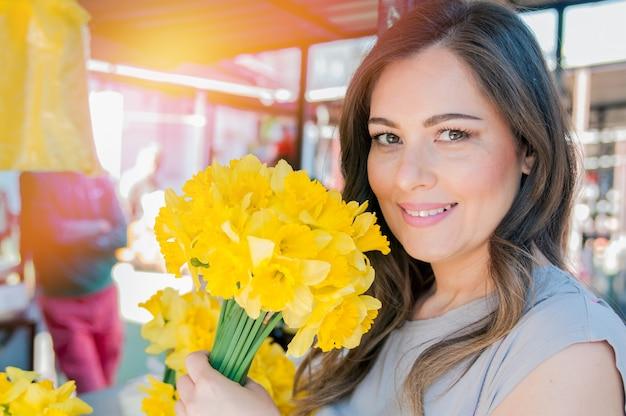 新鮮な花を選ぶ若い笑顔の女性。屋外の晴れた日に新鮮な花市場の屋台に立っている間に楽しんで花の花束を嗅ぐ美しい若い女性のプロフィールの肖像画を閉じます。