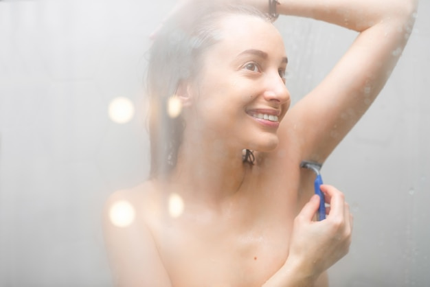Young smiling woman shaving armpits in the shower