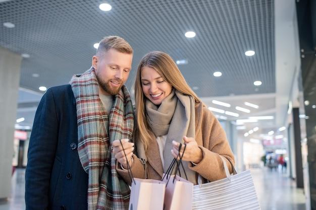 一緒に買い物をしながら、売り場の1つで季節限定セールで買ったものを夫に見せて笑顔の若い女性
