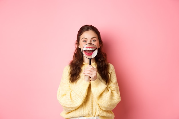완벽하게 하얗게 된 치아를 보여주는 젊은 웃는 여성은 돋보기, 치과 클리닉, 구강 및 의료 개념의 프로모션, 분홍색 배경에 서 있는 미소.
