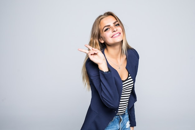 Молодая улыбающаяся женщина показывает изолированные знак победы или мира