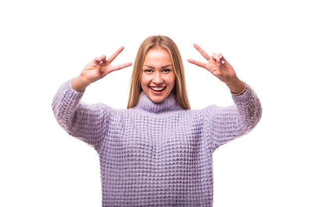 孤立した勝利またはピースサインを示す若い笑顔の女性