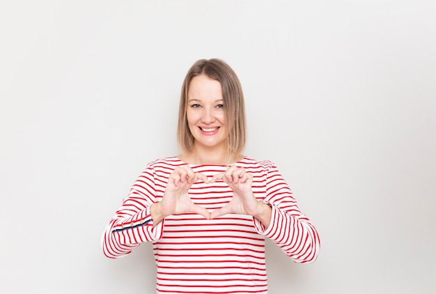Young smiling woman shows heart hand sign.