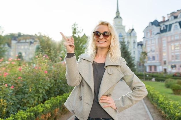若い笑顔の女性は人差し指を示しています、注意アイデアeureka