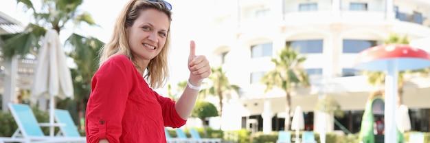 Молодая улыбающаяся женщина сидит у бассейна отеля и показывает палец вверх