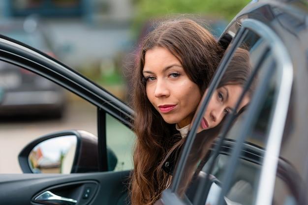 若い、笑顔の女性が開いたドアの車に座って振り返る