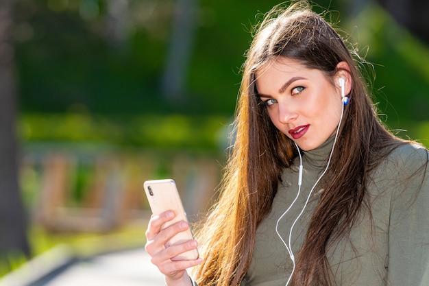 Молодая женщина улыбается сидит на скамейке в парке на улице слушать музыку с наушниками с помощью мобильного телефона в солнечный и ветреный день