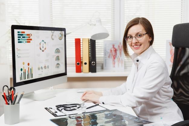 机に座って、病院のライトオフィスで医療文書を使用してコンピューターで作業している若い笑顔の女性