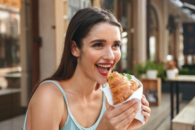 クロワッサンを食べながら屋外のカフェに座っている若い笑顔の女性