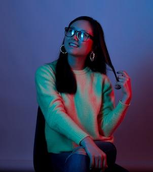 의자에 앉아 젊은 웃는 여자는 빨간색과 파란색 빛으로 켜져 있습니다