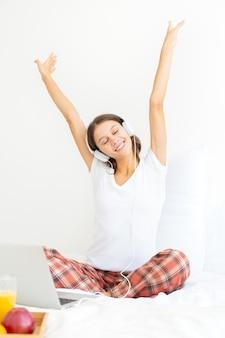 Молодая улыбающаяся женщина сидит на кровати в спальне и слушает музыку