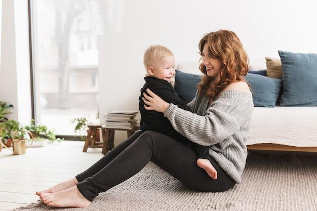 彼女の小さなハンサムな息子と楽しく遊んで床に座っている若い笑顔の女性